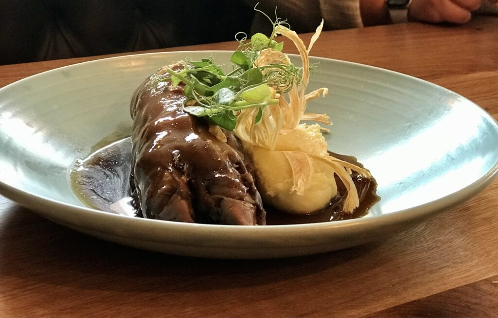 the yard braised pigs trotter stuffed with chicken mousse ham creamed potatoes onions